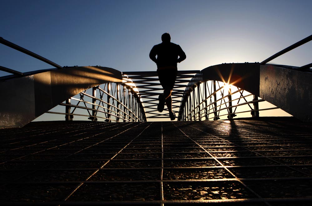 A jogger runs over a pedestrian bridge towards Lake Michigan on an early morning.